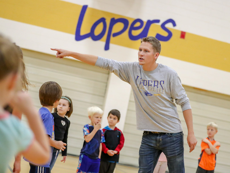 UNK student instructing school age students in gym