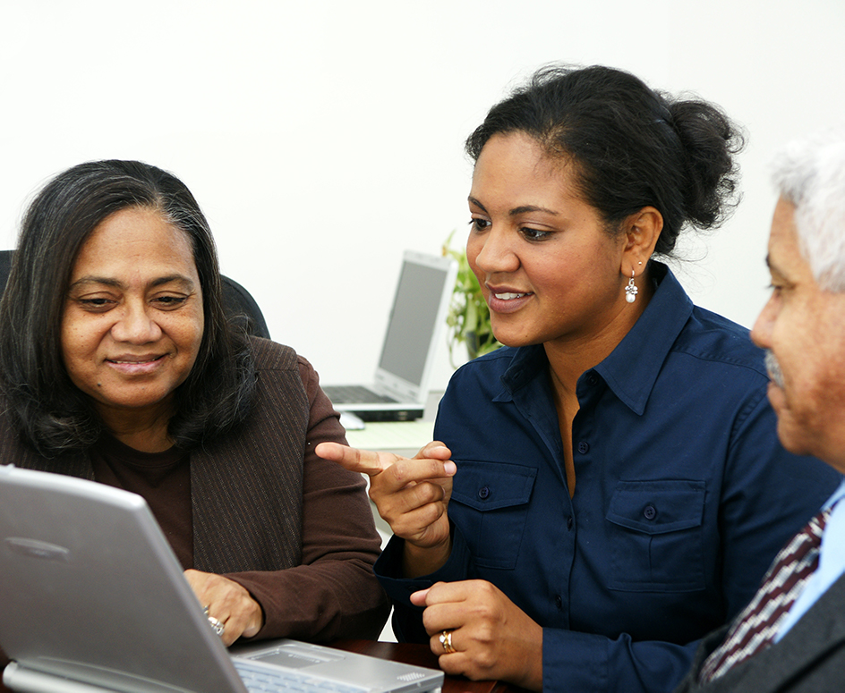 Minority businesspeople surrounding a laptop